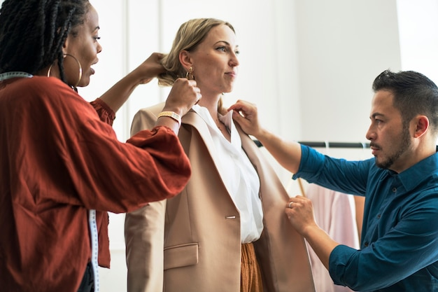 Fashion designers fitting the model in a boutique