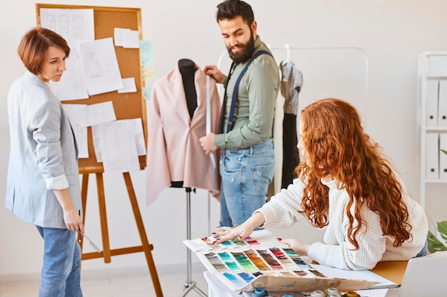 Fashion designers working in atelier with dress form and color palette
