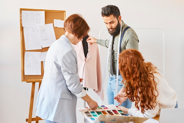 Fashion designers working in atelier with dress form