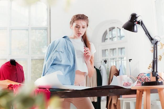 Модельеры, работающие в студии, сидя на столе