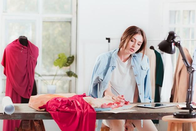Модельеры работают в студии, сидя на столе
