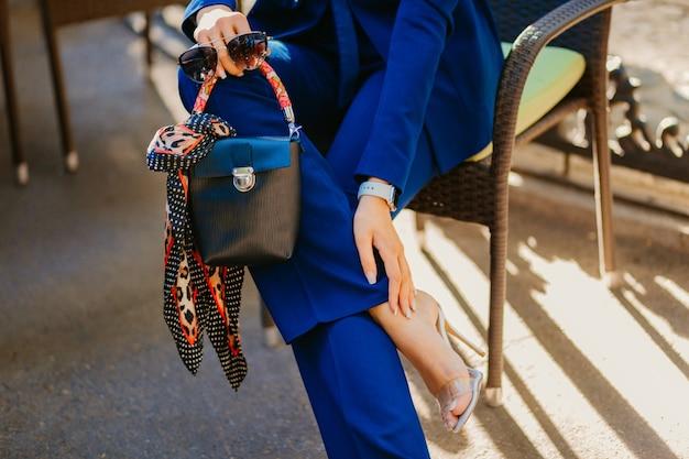 Модные детали и аксессуары элегантной женщины, одетой в синий костюм