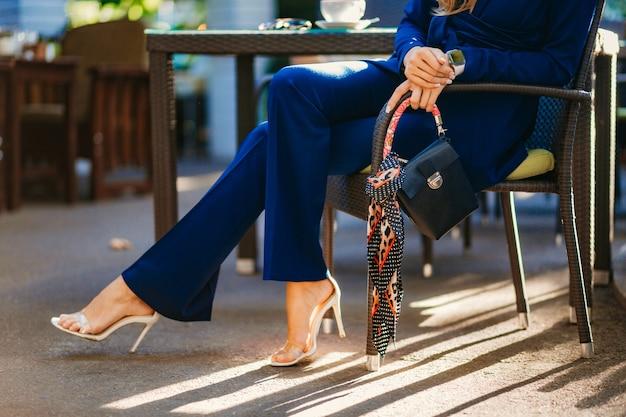 青いスーツに身を包んだエレガントな女性のファッションの詳細とアクセサリー