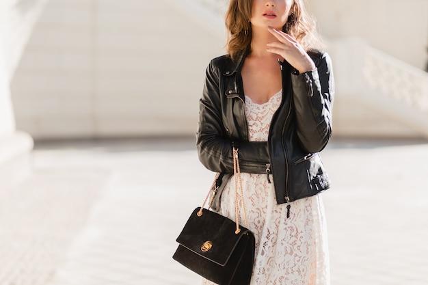 Dettagli di moda da vicino della donna attraente che cammina in strada in abito alla moda, che tiene la borsa suude, indossa una giacca di pelle nera e abito di pizzo bianco, stile primavera autunno