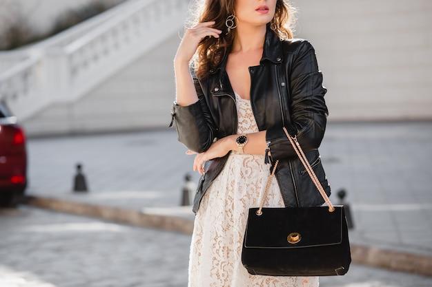 패션 세부 사항은 검은 가죽 재킷과 흰색 레이스 드레스, 봄 가을 스타일을 입고 지갑을 들고 유행 복장에서 거리에서 산책하는 매력적인 여자의 닫습니다