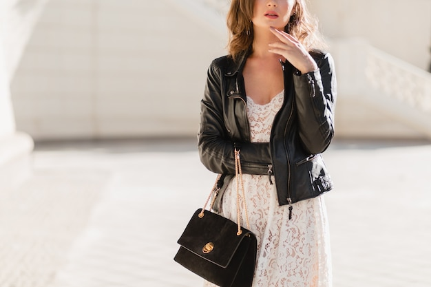 패션 세부 사항은 검은 가죽 재킷과 흰색 레이스 드레스, 봄 가을 스타일을 입고, suude 핸드백을 들고 유행 복장 거리에서 산책하는 매력적인 여자의 닫습니다