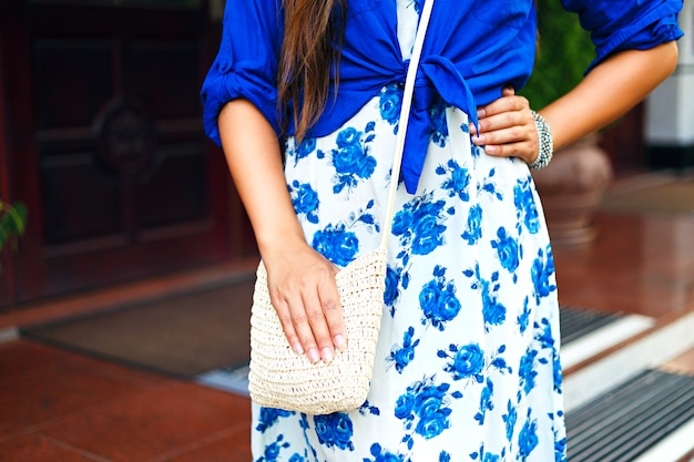 패션 세부 사항, 꽃 무늬 드레스. 세련 된 보석,여자가 그녀의 손에 가방을 들고 톤 색상, 스트리트 스타일.