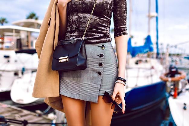 섹시한 치마, 베이지 색 코트를 입고 고급 가죽 가방과 선글라스를 들고 봄 가을 시즌 중반에 요트가있는 럭셔리 마리나 근처의 거리에서 포즈를 취하는 여성의 패션 세부 정보.