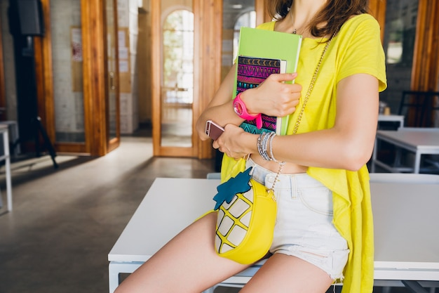 Fashion details of of young pretty woman sitting at table at study room holding notebooks in hands, student learning, education, colorful summer hipster style, purse