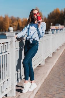 Fashion dressed woman holding a cup of coffee