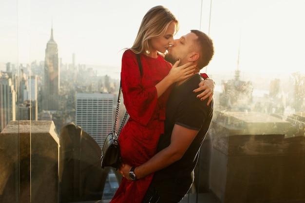 패션 옷을 입은 젊은 부부는 뉴욕시의 록펠러 센터 꼭대기에 서 있습니다.