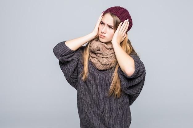 Модно одетая молодая модель имеет голову и боль в животе на сером