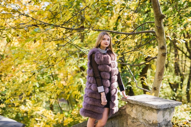 Fashion dresses woman in fur coat and dress posing in autumn park