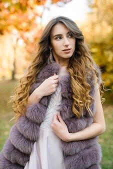 ファッションドレスの女性の毛皮のコートと秋の公園でポーズをとるドレス