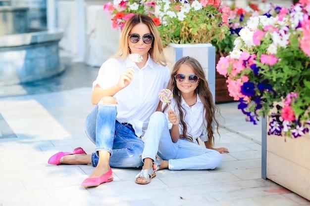 ファッション家族概念-スタイリッシュな母と子の摩耗。幸せな家族の肖像画:彼女の小さなかわいい娘を持つ若い美しい女性。若い娘は秋の市屋外で母親を抱擁します。