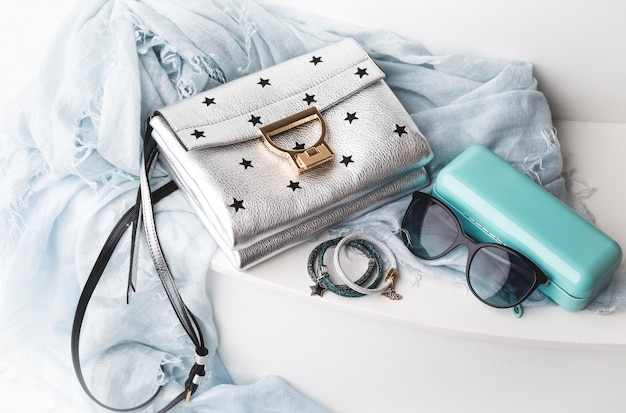 Fashion female accessories. handbag with sunglasses and scarf