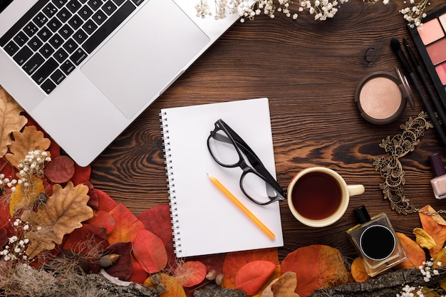 Fashion female accessories set. autumn leaves, paper notebook and laptop
