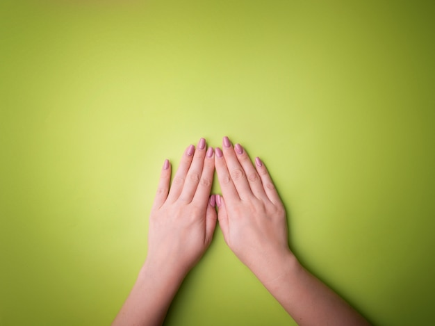 Fashion, female hands with manicure, nail care, healthy skin and natural cosmetics. top view contrasting against a green background.