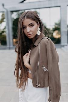긴 검은 머리와 누드 패션 여성 모델은 따뜻한 날씨에 도시 배경에 장난스럽게 포즈를 취하는 좋은 분위기에서 야외 포즈를 취합니다. 거리에 코트에 매력적인 검은 머리 소녀