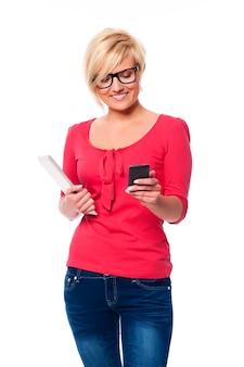 Moda femminile utilizzando il telefono cellulare e tenendo la tavoletta digitale
