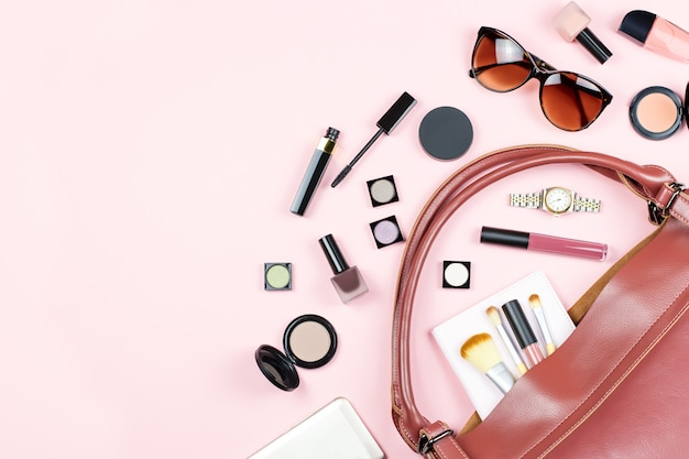 Fashion flat lay with beauty products and accessories on pink background