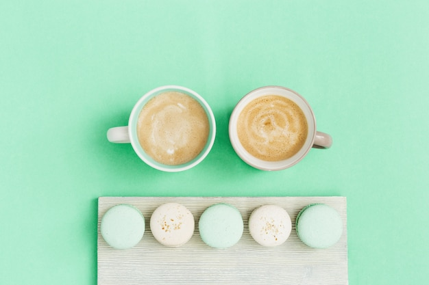 Fashion flat lay with two cup of coffee and tasty macaroons. sweet food and hot cappuccino in big mug. morning concept. top view.