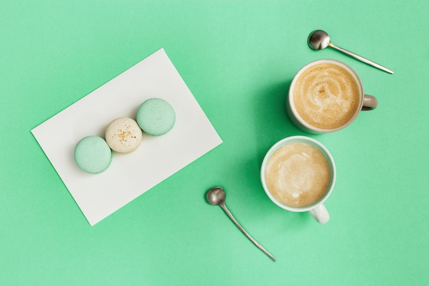 Fashion flat lay with two cup of coffee and tasty macaroons on trend color mint. sweet food and hot cappuccino in big mug. winter morning concept. top view.