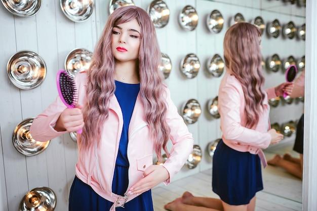 패션 괴물. 매력적인 합성 소녀, 빈 모양과 긴 라일락 머리카락을 가진 가짜 인형이 스튜디오에서 분홍색 헤어 브러시를 들고 있습니다. 전구 및 거울 근처 파란 드레스에 세련 된 아름 다운 여자