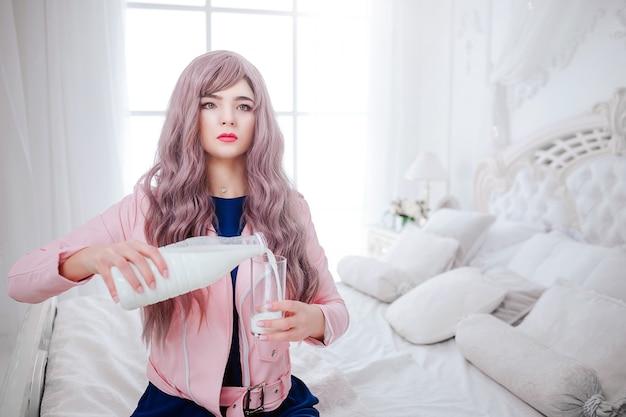 패션 괴물. 매력적인 합성 소녀, 빈 모양과 긴 라일락 머리카락을 가진 가짜 인형이 흰색 침실에 앉아있는 동안 유리에 우유를 붓고 있습니다. 파란 드레스에 세련 된 아름 다운 여자입니다.