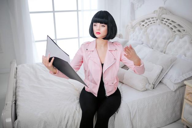 패션 괴물. 매력적인 합성 소녀, 빈 표정과 짧은 검은 머리카락을 가진 가짜 인형이 침대에 앉아있는 동안 폴더를 잡고 있습니다. 백색 침실에 분홍색 재킷에 세련 된 여자. 패션과 뷰티