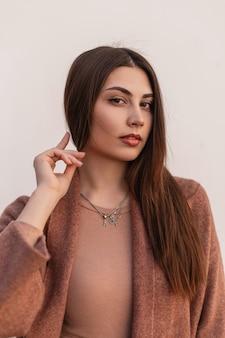 패션 신선한 초상화 우아한 코트에 긴 갈색 머리를 가진 자연스러운 메이크업으로 섹시 한 입술으로 아름 다운 예쁜 젊은 여자. 흰색 벽 근처 야외에서 포즈 관능적 인 귀여운 소녀 모델.