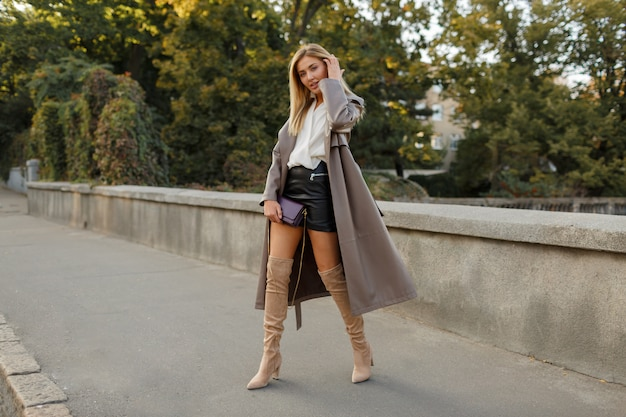 Fashion full length image of elegant  blond  woman in stylish luxury beige leather  coat and hight heels, walking  outdoor