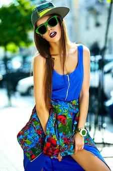 Adatti a fascino il modello alla moda sorridente sexy alla moda della giovane donna bella in vestiti blu dell'estate dei pantaloni a vita bassa nella via in cappuccio