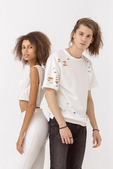 白い背景でポーズをとってアウトレット服のファッションの女の子と男。スタイリッシュなカップル。綺麗な