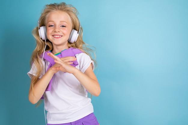 Модная девушка-блондинка с длинными волосами в спортивной рубашке, шортах, кедах стоит, слушает музыку в наушниках, танцует и улыбается