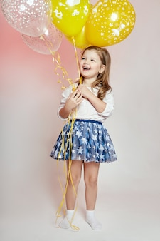 風船、子供ファッション、衣類とファッションの女の子の子供のお祝い。ポーズの女の子