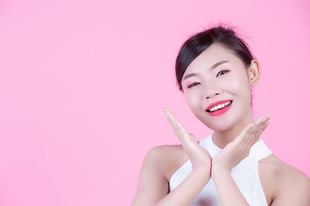 패션 소녀는 분홍색 배경에 손 제스처와 함께 드레스.