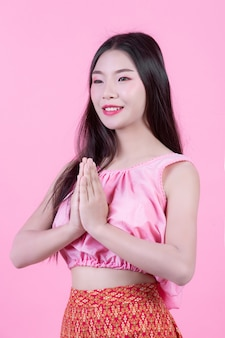 Fashion girl dress up with hand gestures on a pink background.