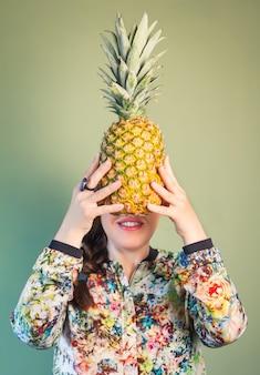 顔の前にパイナップルを保持しているファッションの女の子