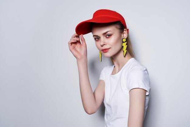 赤い帽子の黄色いイヤリングの夏のファッションスタジオのファッションの女の子