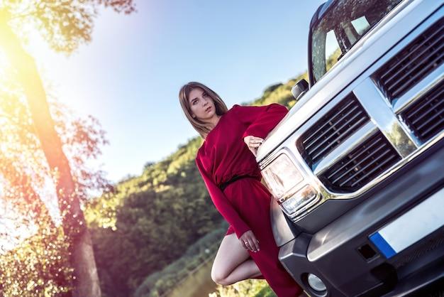 그녀의 현대 자동차 근처에 서 있는 세련된 빨간 드레스를 입은 패션 소녀와 자연을 휴식