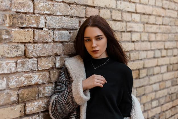 Модная девушка в модной одежде позирует на улице