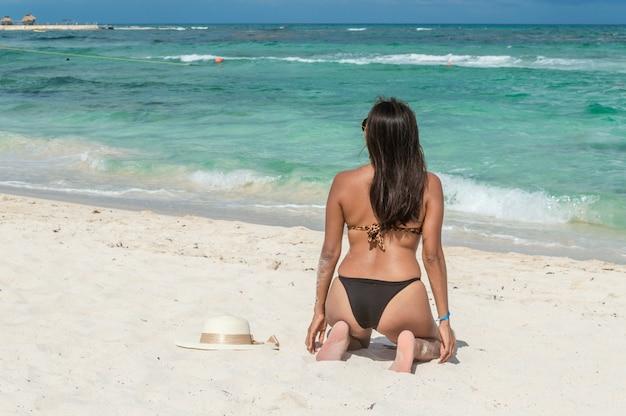 美しい午後に青い海を見て砂の上にひざまずいてファッションの女の子。彼女の背中に水着を着ている女性。海を見て魅力的な女性の裏。砂の上の弓で太陽の帽子。