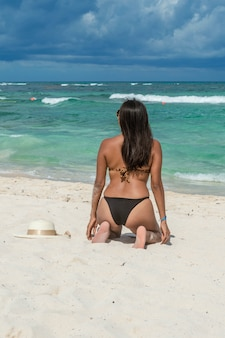 Fashion girl kneeling on the sand looking at the blue sea on a beautiful afternoon. woman wearing swimsuit on her back. back of attractive woman looking at the sea. sun hat with bow on the sand.