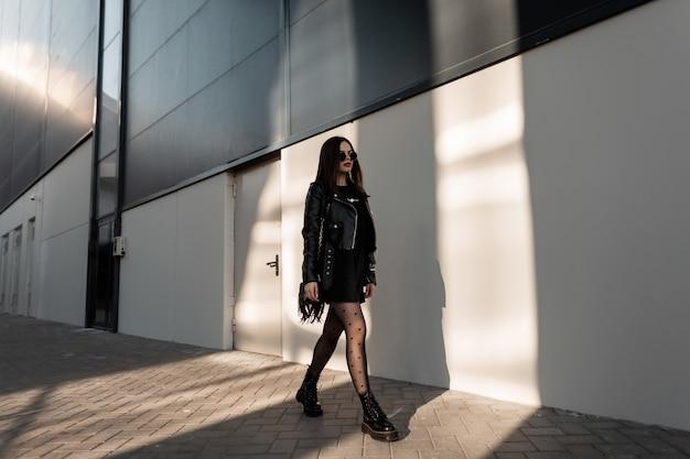 최신 유행하는 검은 옷에 선글라스를 끼고 가죽 재킷과 섹시한 스타킹에 핸드백을 신은 패션 걸 모델은 햇빛 아래 현대적인 건물 근처 거리를 걷습니다. 도시 여성 스타일