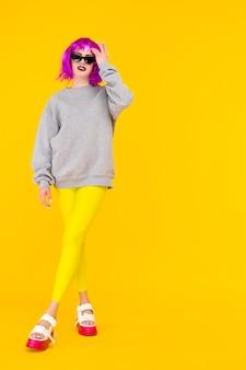 Портрет девушки моды на желтом фоне. сумасшедший стиль молодой женщины в розовом парике