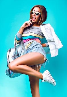 スマートカジュアルなスポーツ服、ビジネススタイル、甘いパステルカラー、サングラス、バックパックデニムとジャケット、ミントの背景、スタイリッシュな女性を着て、スタジオでポーズのファッションの女の子。
