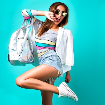 Модная девушка позирует в студии, в элегантной повседневной спортивной одежде, деловом стиле, сладких пастельных тонах, солнцезащитных очках, джинсовой ткани рюкзака и куртке, мятном фоне, стильной женщине.