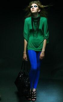 Девушка моды позирует на темном фоне