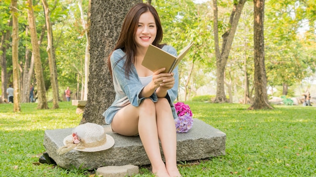 ファッションの女の子は庭の公園で読む